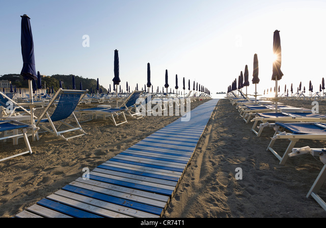 Italy, Liguria, Sestri Levante, Row of outdoor chairs and sunshade on beach - Stock Image