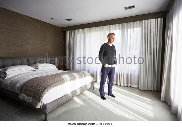 Sad mature man standing in bedroom. - Stock Image