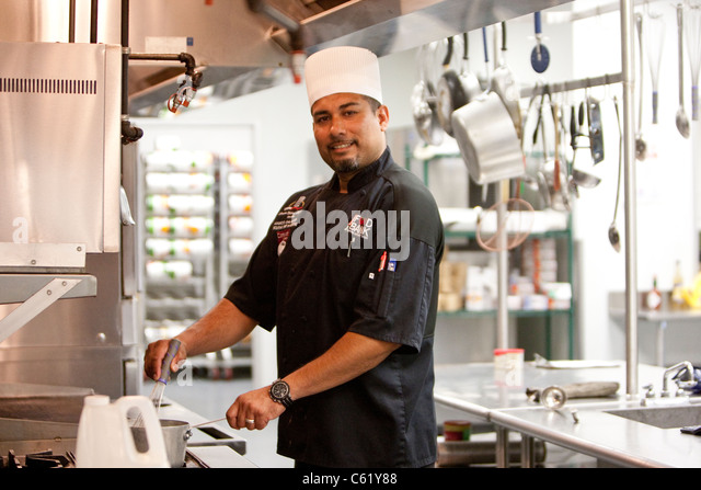 Hispanic male chef works in the kitchen of the San Antonio Food Bank in San Antonio, Texas - Stock Image