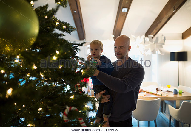 Father and son decorating Christmas tree - Stock Image