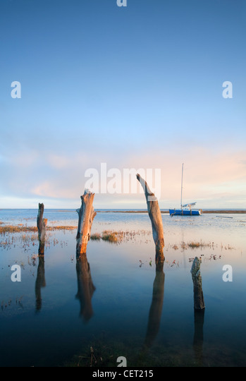 Thornham Harbour and the remains of an ancient wooden pier at high tide on the North Norfolk Coast. - Stock-Bilder