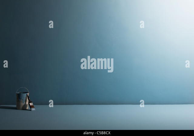 Paint pot and paintbrush on blue background - Stock Image