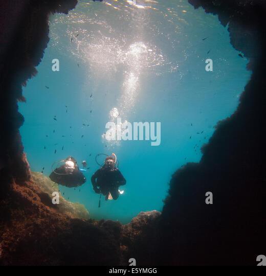 Scuba divers swimming underwater in bright blue Mediterranean Sea - Stock Image