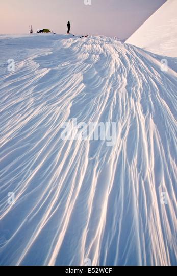 Climber enjoys the sunset light atop wind formed sastrugi formations, Chugach National Forest, Alaska - Stock Image