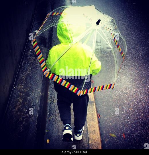 Little boy walking under the rain with his transparent umbrella - Stock-Bilder