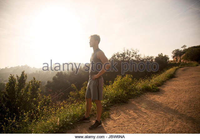 Young man outdoors, wearing sports clothing, taking a break from workout, looking at view - Stock-Bilder