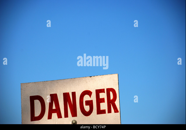 White sign with red type saying DANGER with blue sky in background - Stock-Bilder
