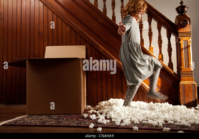 Girl playing with packing material from cardboard box - Stock Image