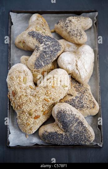 Heart shaped bread rolls on tray - Stock Image