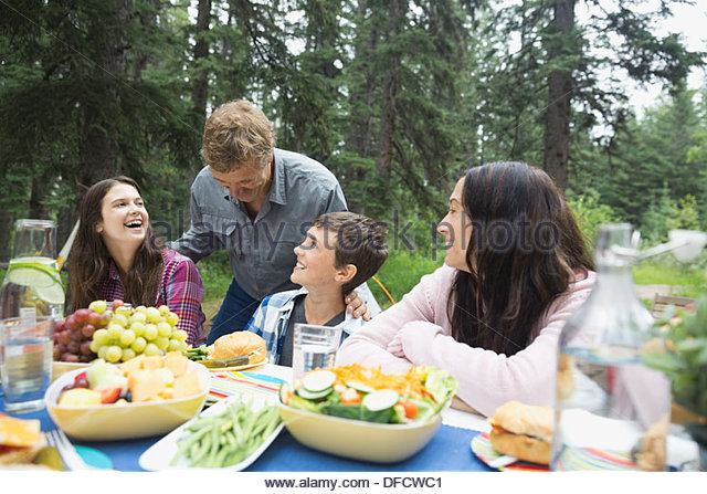Happy family enjoying meal at campsite - Stock Image