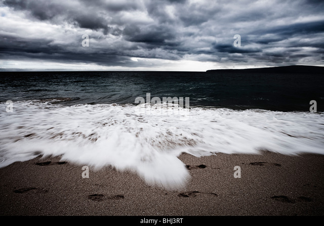 Waves crashing on beach with footprints - Stock Image