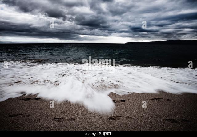 Waves crashing on beach with footprints - Stock-Bilder
