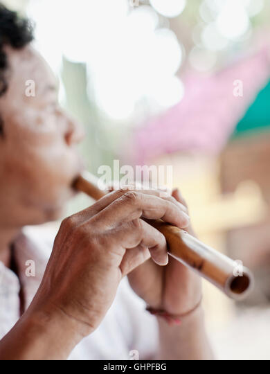 Wind instrument maker Yim Seychot plays a Cambodian horn (snaeng) at his home outside Phnom Penh, Cambodia. - Stock Image