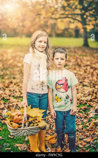 two siblings standing in autumn park - Stock Image