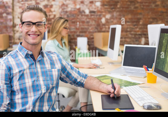 Happy male photo editor using computer in office - Stock Image