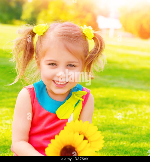 Adorable sweet child with sunflowers bouquet having fun in the garden, little girl enjoying summer nature, happiness - Stock Image