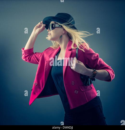 Urbane mature woman wearing a sunglasses and hat, studio shot - Stock Image