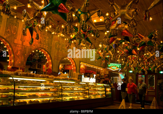 Mi Tierra Bakery baked goods counter with customers and display with overhead decor mexican pinatas San Antonio - Stock Image