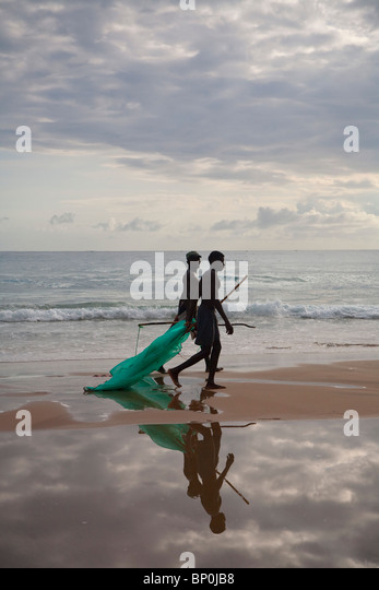 Mozambique, Tofo. Two fishermen walk with their nets along the beaches at Tofo. - Stock Image