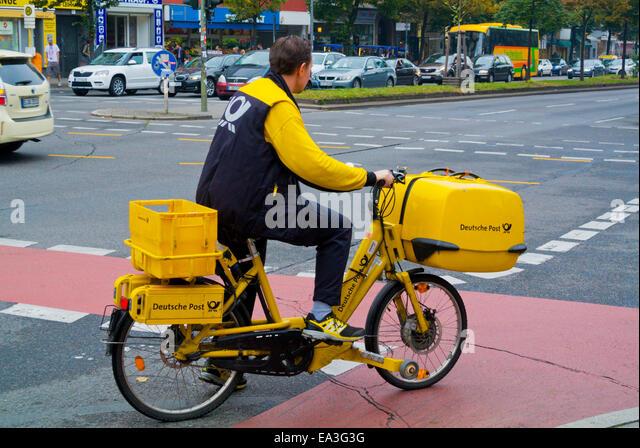 Deutsche Post, German postal company, postman on bike, Kreuzberg, west Berlin, Germany - Stock Image