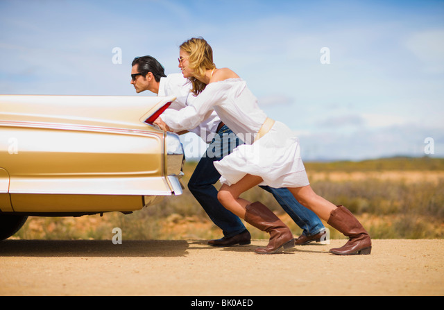 Couple pushing a car - Stock Image