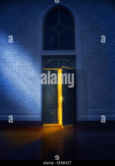 Opening door with yellow glow in the church at night - Stock Image