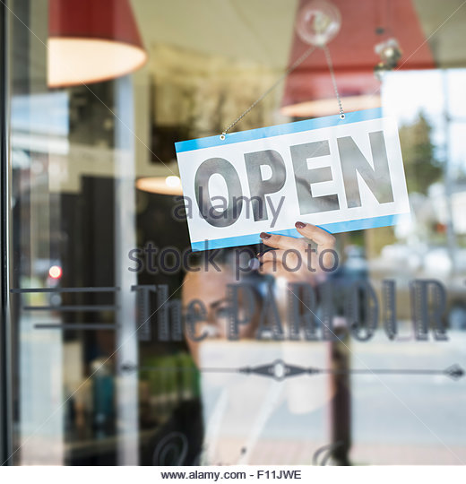 Hairdresser turning open sign in retro barbershop window - Stock Image