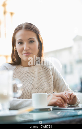 Portrait of young woman at sidewalk cafe - Stock-Bilder