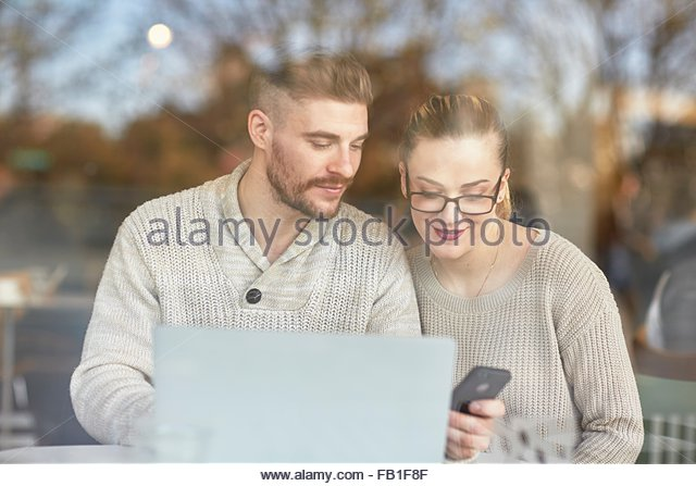 Young man and woman sitting in cafe, using laptop and smartphone - Stock-Bilder
