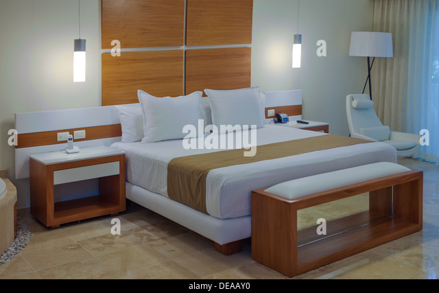 Bedroom interior in a house or hotel with minimalist decor in neutral tones and a large double bed - Stock Image