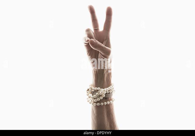 Studio shot of mature woman's hand making peace gesture - Stock-Bilder