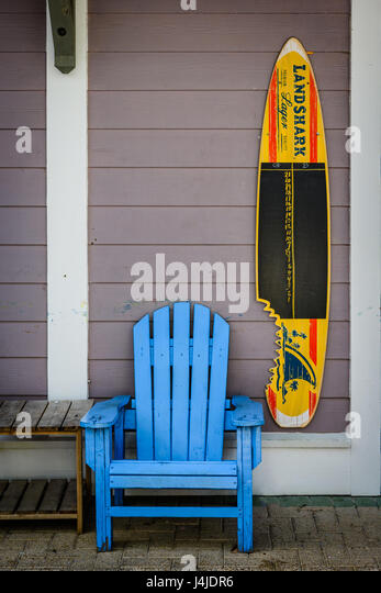 A bright blue Adirondack chair sits next to a surfboard with advertising for bear, in a courtyard of a small shopping - Stock Image
