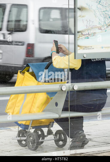 female postwoman in uniform with mailbag waiting for bus. - Stock Image