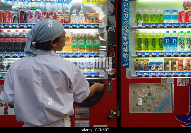 A man buying soft drink from an automatic vending machine Tokyo Japan - Stock Image