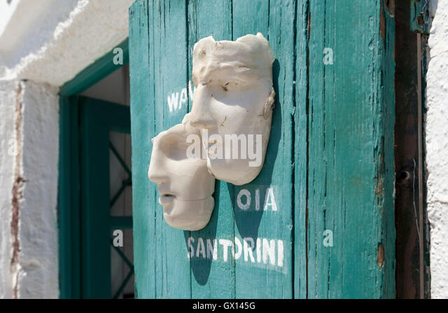 Porcelain masks for sale in Oia, Santorini against a weathered  green wooden door. - Stock Image