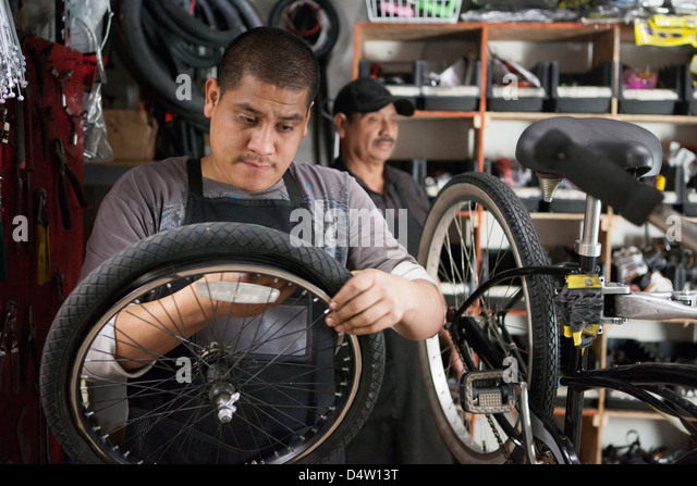 Mechanic working in bicycle shop - Stock Image