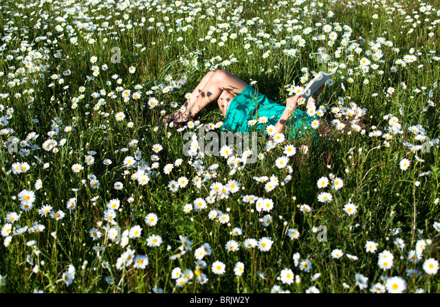 A young woman enjoys a quite moment reading a book in a field of wildflowers in Idaho. - Stock Image
