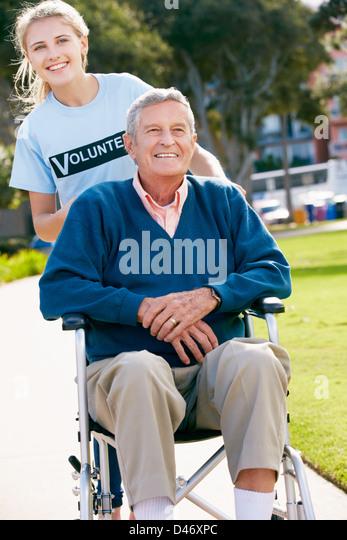 Teenage Volunteer Pushing Senior Man In Wheelchair - Stock Image