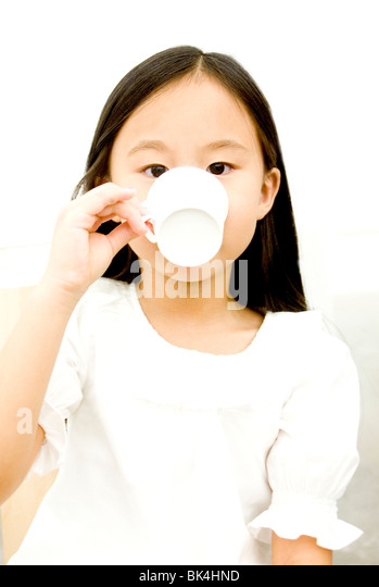 Young asian girl sipping from a tea cup - Stock Image