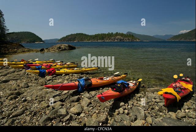 Empty kayaks lie pulled up along the shoreline of Desolation Sound. Desolation Sound, British Columbia, Canada. - Stock-Bilder