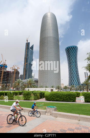 Corniche cyclists  and  office towers in business district of Doha in Qatar, Middle East - Stock Image