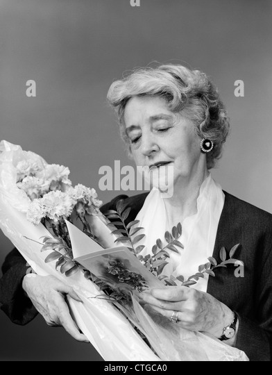 1950s 1960s ELDERLY WOMAN RECEIVING A BOUQUET OF CARNATIONS READING THE CARD - Stock Image