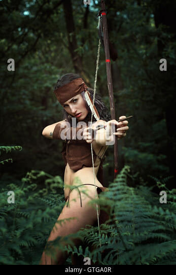 Wild huntress with bow in the woods. Power and survival - Stock-Bilder