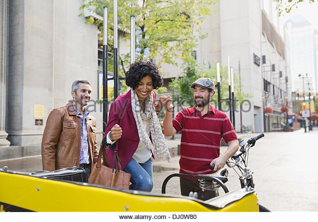 Driver assisting woman into rickshaw - Stock Image