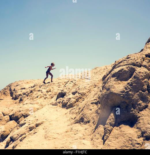 Young boy climbing sandy hill, Hurgada, Red Sea, Egypt - Stock Image