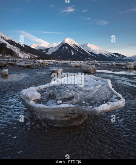 Stranded ice floes at low tide on the Turnagain Arm with alpenglow on the Chugach Mountains in the background, Alaska, - Stock Image