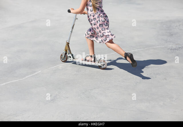 girl practicing riding kick scooter on road. toy, leisure, playing, balance. traffic danger - Stock Image