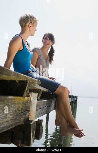 Germany, Bavaria, Ammersee, Two young women sitting on jetty - Stock-Bilder