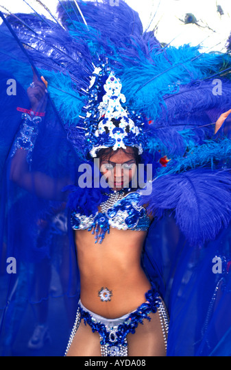 Trinidad Carnival woman in colorful costume wining dancing blue feathers - Stock Image