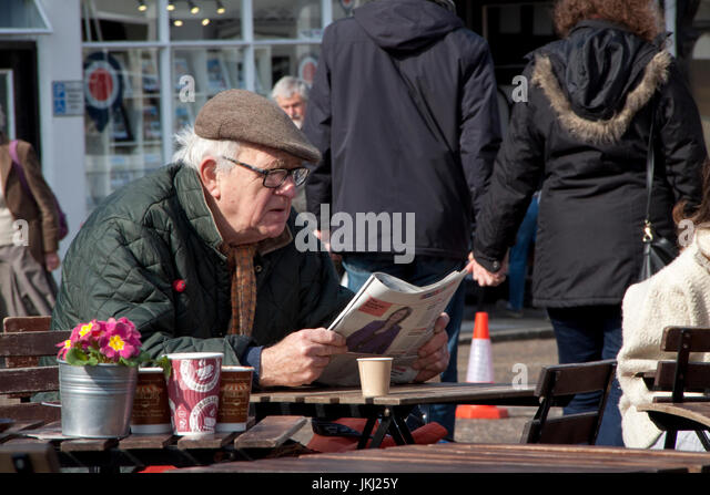 Senior man intently reads a newspaper at an outside cafe - Stock Image